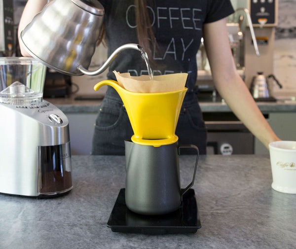 a woman pouring water into pourover