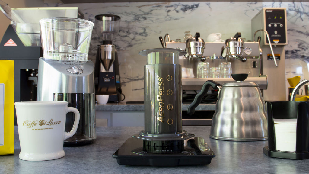 aeropress coffee maker displayed in the center with various brewing equipment at its sides