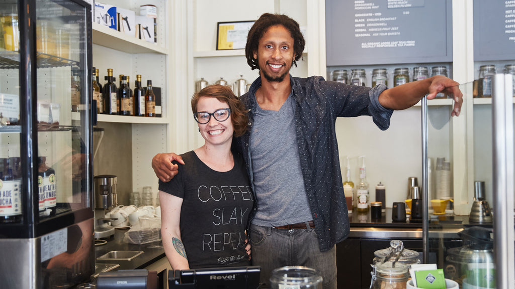 two baristas smiling directly at the camera, while in a friendly embrace