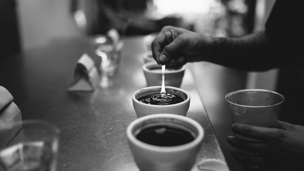 a black & white photo of a person putting a spoon into a cupping bowl