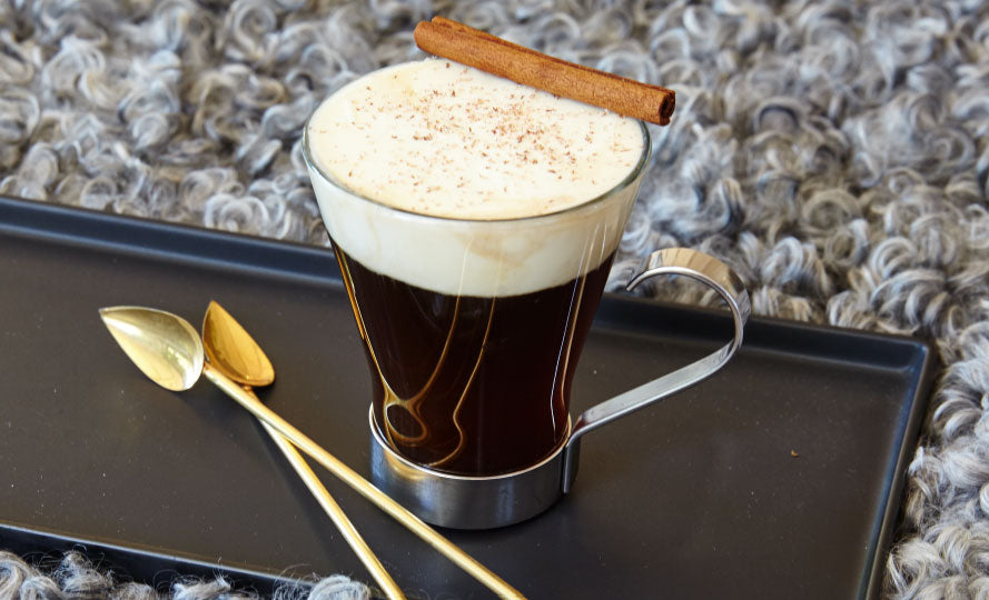 irish coffee in a clear glass with a large head of cream and a cinnamon stick resting on the edge