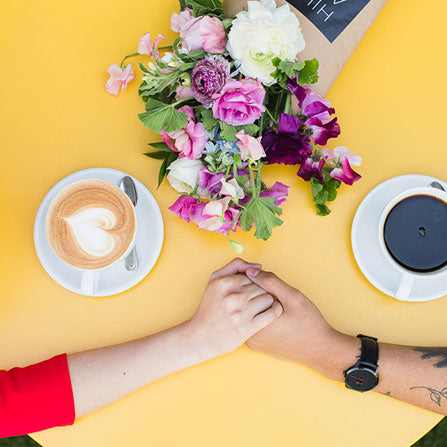 couple holding hands on a yellow table with coffee cups