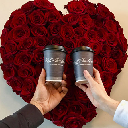 two people holding caffe luxxe coffee cups in front of a heart rose bouquet