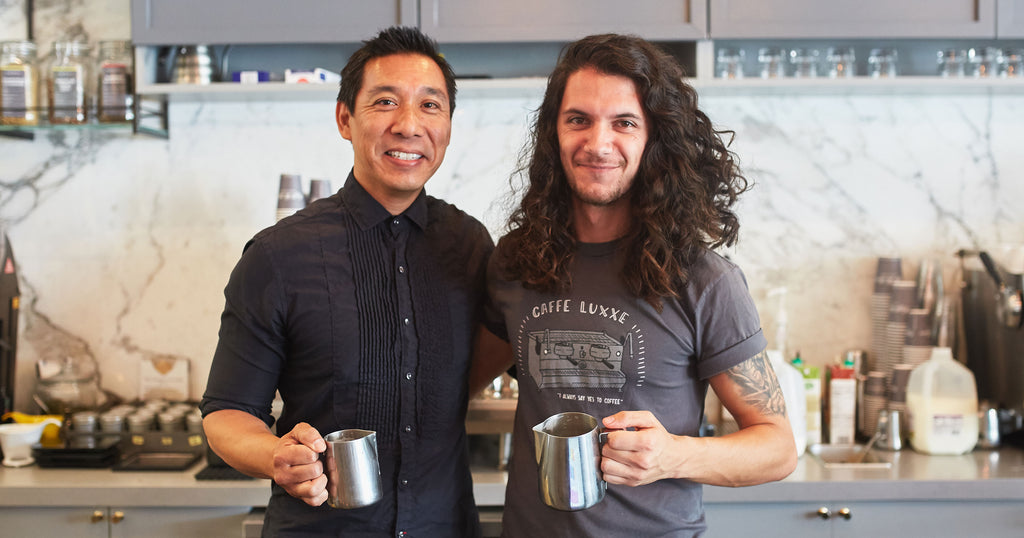 two baristi smiling
