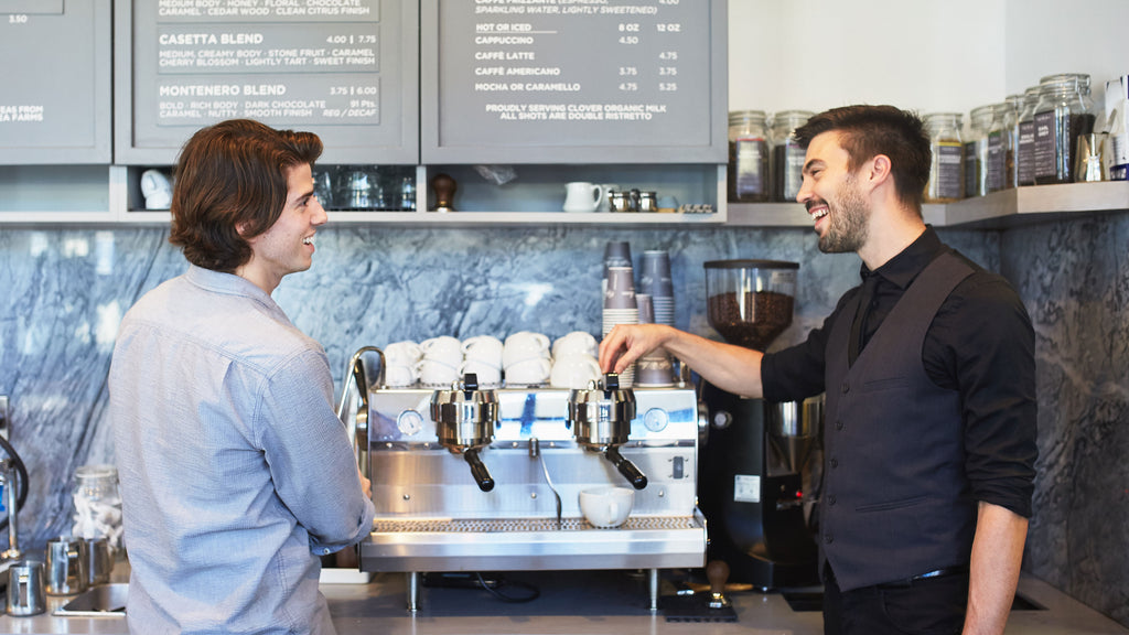 two people together on an espresso machine at caffe luxxe pacific palisades while smiling at each other