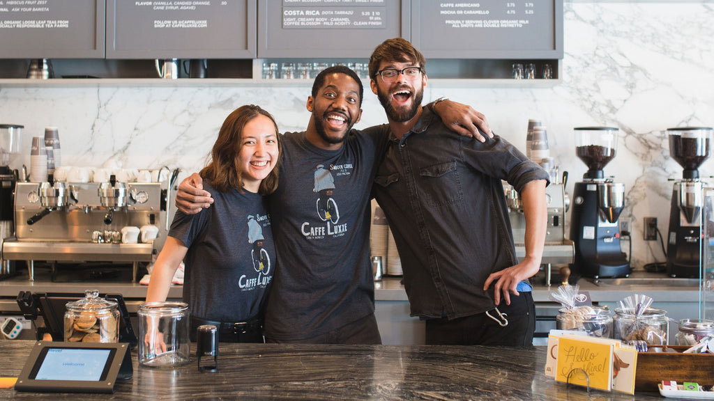 three baristas behind bar at caffe luxxe