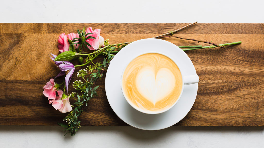 a latte with heart latte art sitting atop a wooden board with flowers directly above the latte