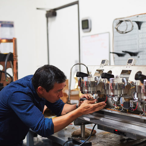a personin a blue shirt fixing an espresso machine