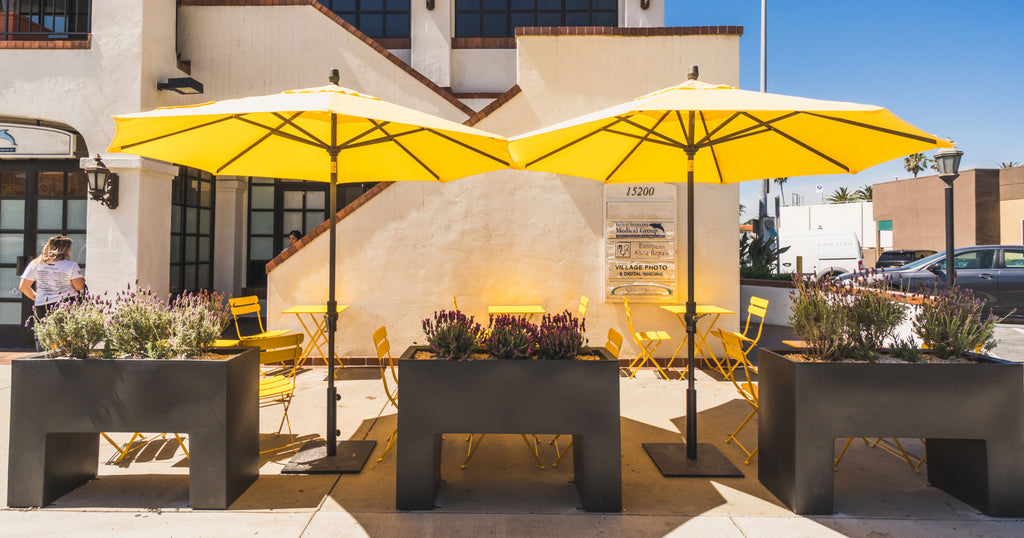 exterior of caffe luxxe palisades where two large yellow umbrellas cover a seating area