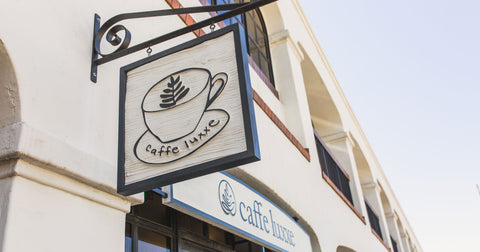 a caffe luxxe sign hanging from a building
