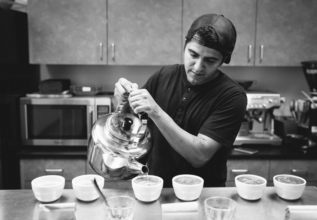 black & white photo of man preparing a coffee cupping