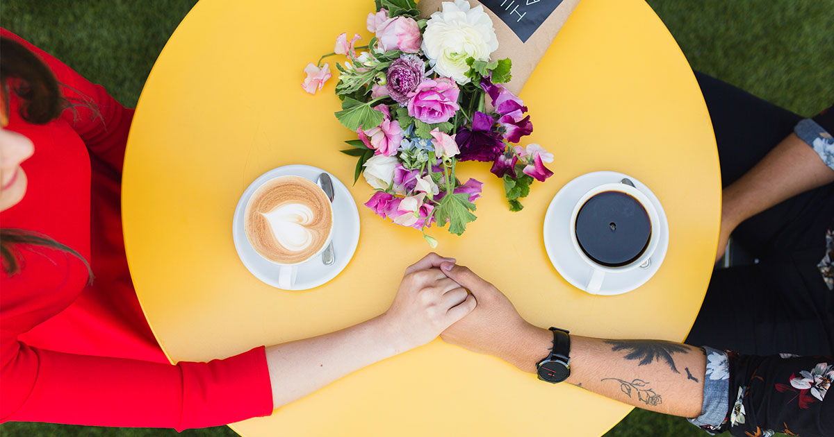 couple holding hands on a yellow table with coffee