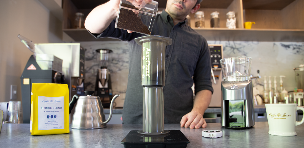 a person pouring ground coffee into an aeropress