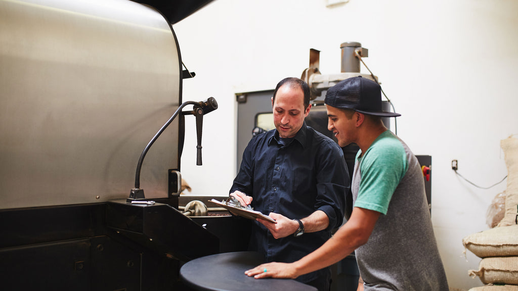 two people in front of a roasting machine looking at a clipboard
