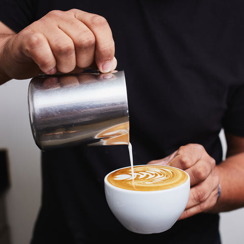 a person in a black shirt pouring latte art