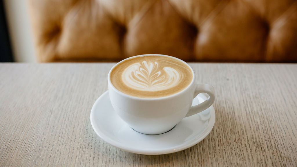 a latte with rosetta latte art sitting on a light grey colored table in front of a leather couch
