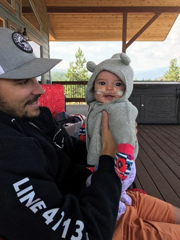 a dad holding his baby on a deck. Both dad and baby are bundled up. Baby is on oxygen and smiling at the camera.