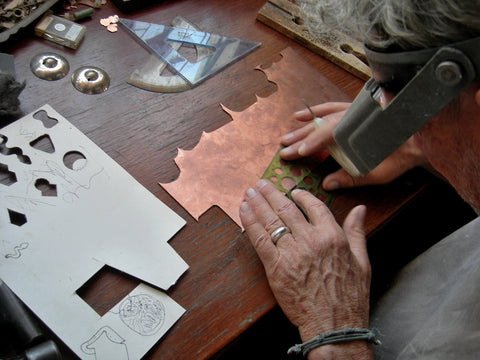 First, a variety of shapes for earrings & pendants are scribed on the copper sheet.