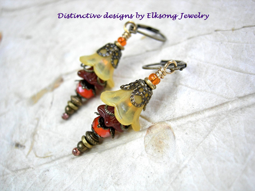Elegant floral earrings in warm, tequila sunrise colors. Golden orange resin & glass flowers, crystal & antiqued brass.