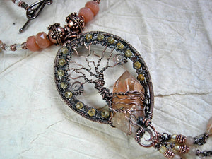 Rich orange & copper strung bead necklace with an ornate copper wire wrap tree & tangerine quartz crystal focal.