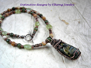 An earthy, unisex necklace, Jade Warrior is hand carved jadeite with oxidized copper wire wrap. Strung bead necklace of jade, fossilized coral, prehnite & copper.