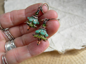 Faery couture flower earrings with green glass & resin flowers, copper caps & beads and Swarovski crystals.