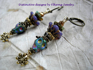 Colorful sugar skull earrings in a rainbow mix. Colored hematite skulls, glass flowers & crystal. Antiqued brass & gold details.
