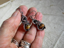 Load image into Gallery viewer, Boho luxe, autumn color earrings with faceted tiger eye & black tourmaline and oxidized copper wire wrap.