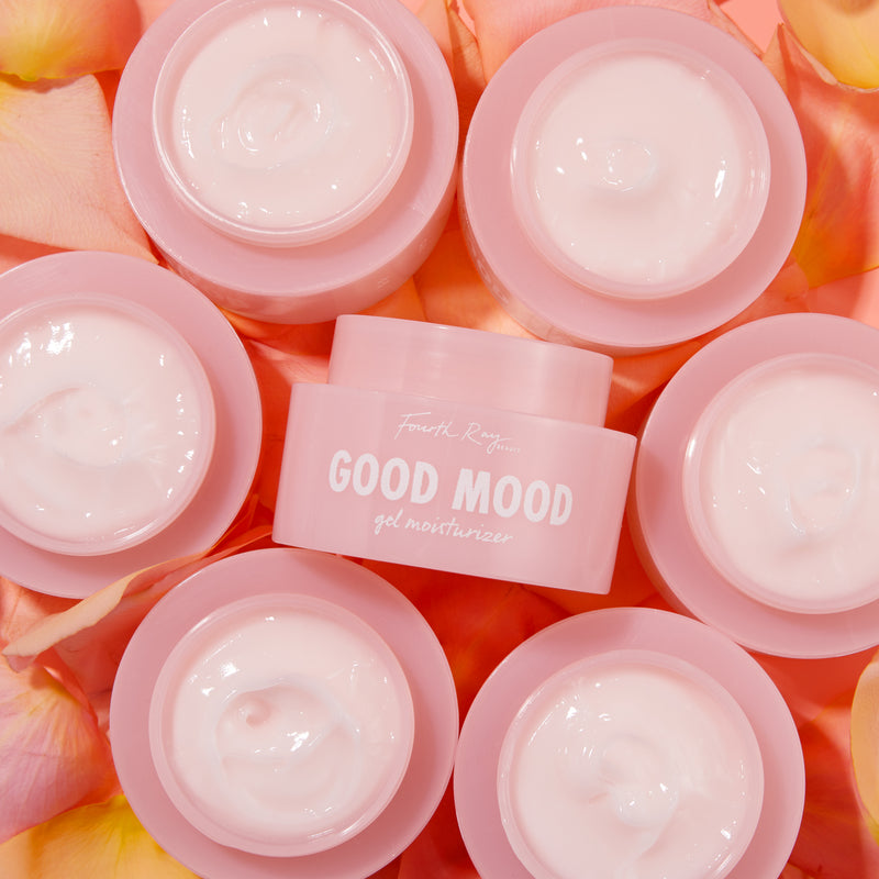 Good Mood gel moisturizer , with multiple good mood products surrounding it; in front of pink/orange  rose petals