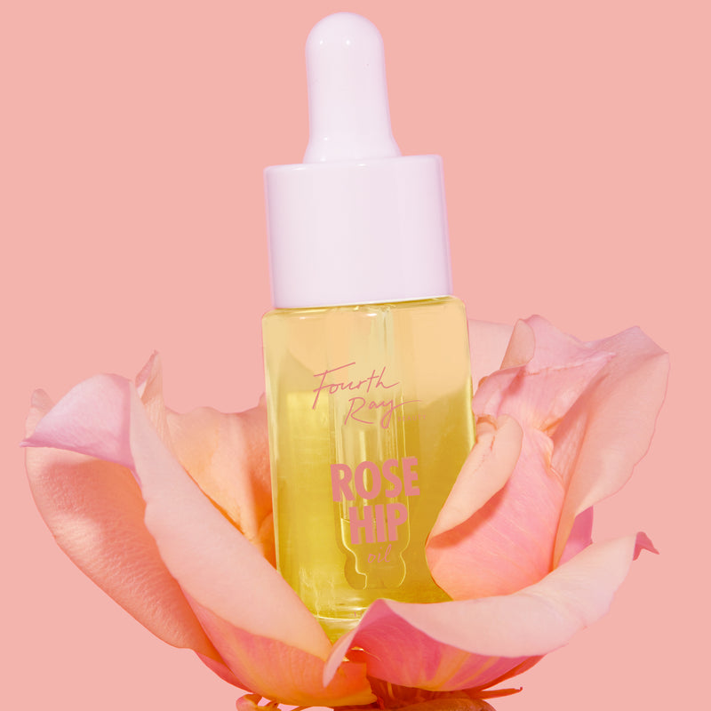 Rose Hip Oil , standing on top on a rose and in a pink background