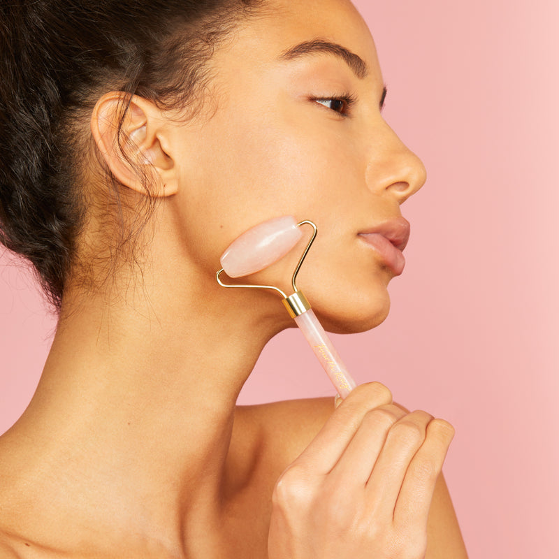 Model using rose quartz roller on her face
