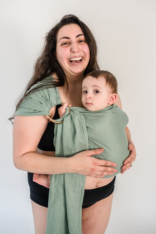 Mother holding toddler in a green ring sling.