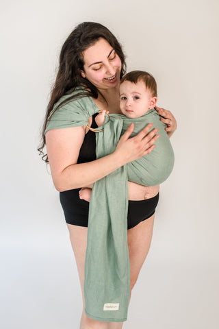 Mother holding toddler in a green fin sling.