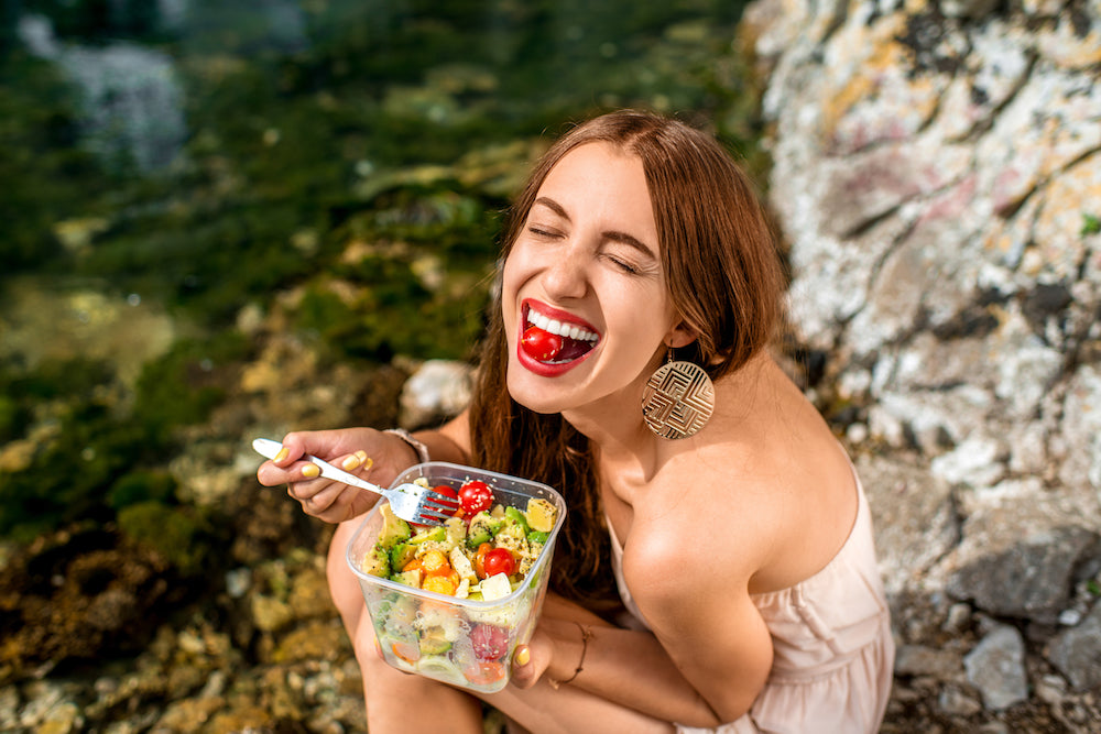 woman laughing eating salad