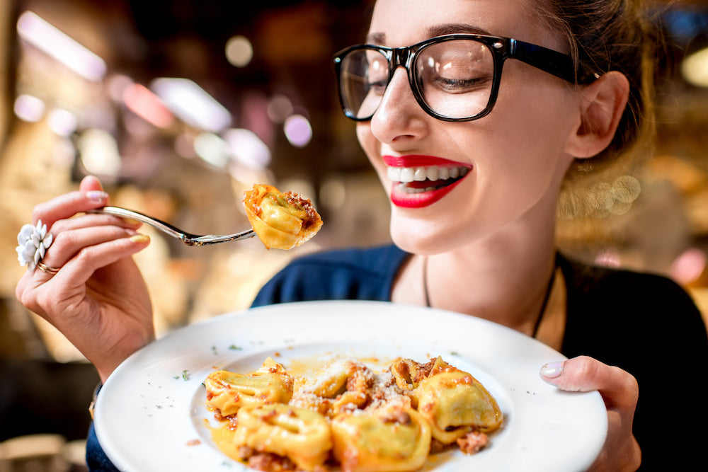 happy woman eating pasta