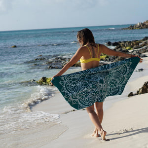 woman standing on shore with arms outstretched holding teal towel with mandala print