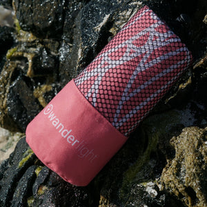 coral pink towel in pouch nestled amongst rocks on the shore