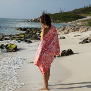 woman standing on shore with coral coloured towel draped over shoulders