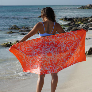 woman standing on shore with arms outstretched holding orange towel with mandala print