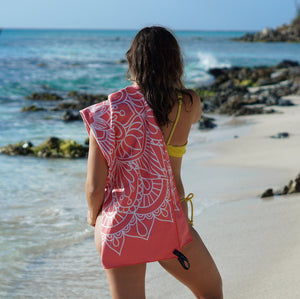 woman in bathing suit with coral mandala towel draped over shoulder looking out along shore