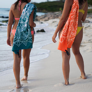 two women walking side-by-side on shore with teal and orange towels draped over shoulder