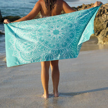 Load image into Gallery viewer, woman standing on shore with arms outstretched holding turquoise towel with mandala print