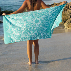 woman standing on shore with arms outstretched holding turquoise towel with mandala print