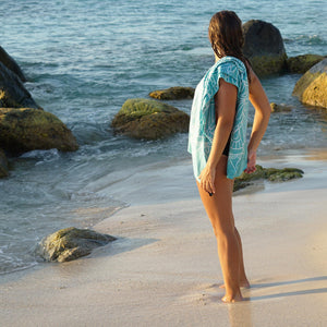 woman standing on rocky shoreline looking out to ocean with turquoise towel draped over shoulder