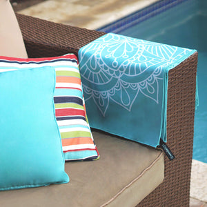 turquoise towel with mandala print folded and draped over the side of a couch arm with pool in background