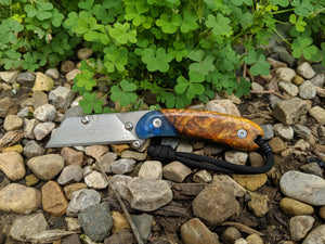 Banzelcroft Customs MEK, titanium EDC utility knife with stabilized chittum burl and blue resin hybrid handle.