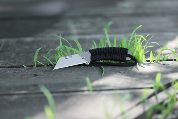 Banzelcroft Customs MEK, a titanium EDC utility knife with black paracord wrapped handle.