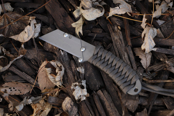 Banzelcroft Customs MEK, a titanium EDC utility knife with dark grey paracord wrapped handle.
