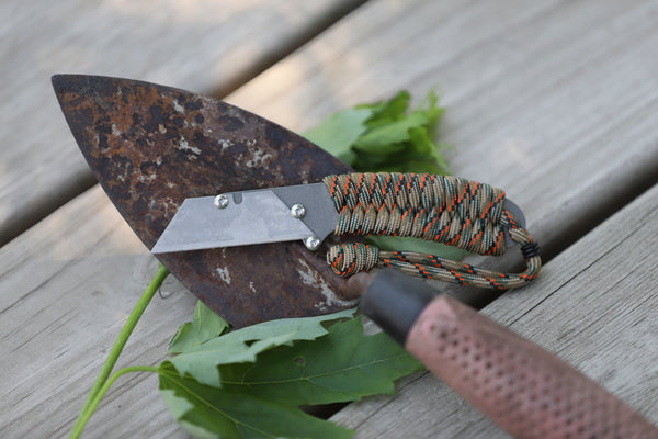 Banzelcroft Customs MEK, a titanium EDC utility knife with fall camo paracord wrapped handle.
