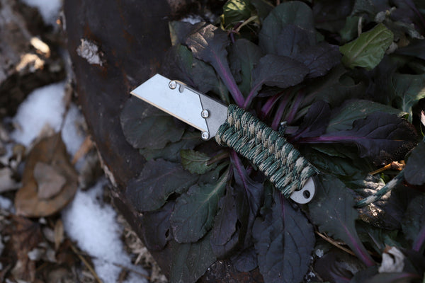Banzelcroft Customs MEK, a titanium EDC utility knife with forest camo paracord wrapped handle.